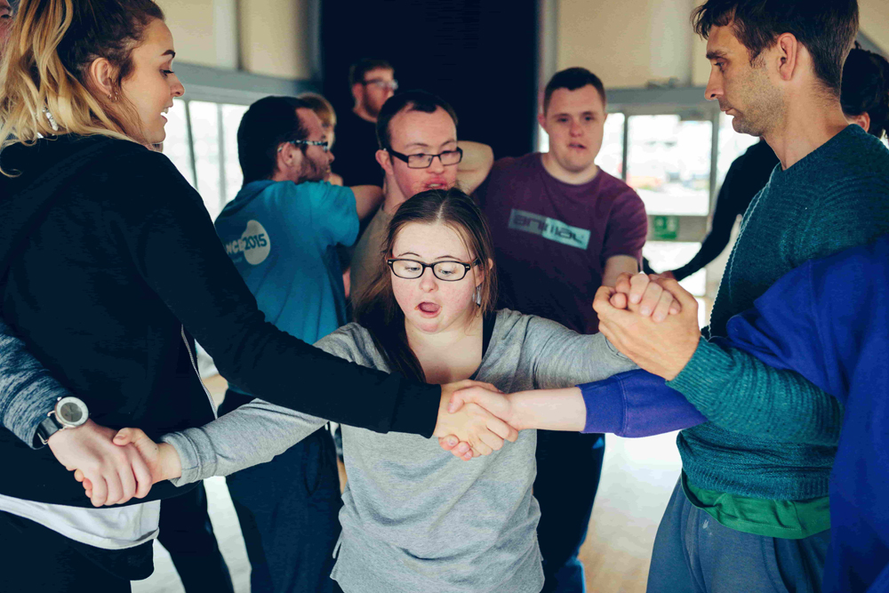 Young people moving around a studio space, arms entwined and holding hands.