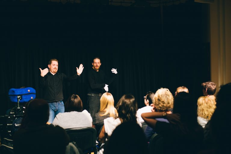 Visual Vernacular artists artists Matthew Gurney and Adam Bassett perform to an audience. Both are making hand and facial gestures, combining performance, mime and comedy.