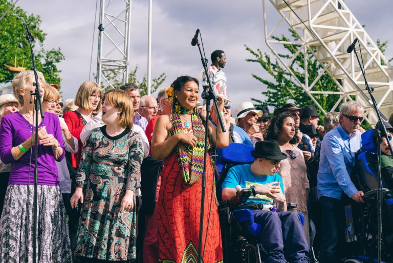 Choir members sing in front of the stage during a performance of Weighting in Bristol's Castle Park