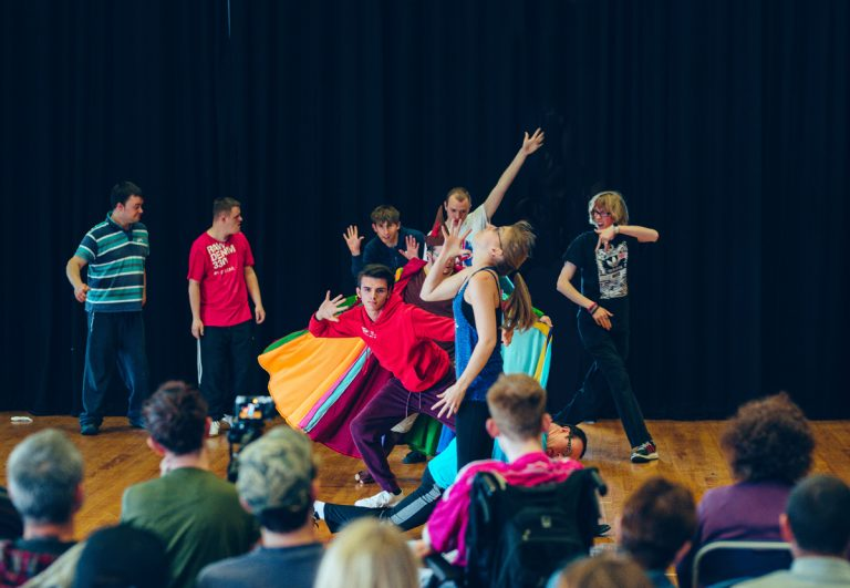Young people performing in front of an audience, moving and dancing.