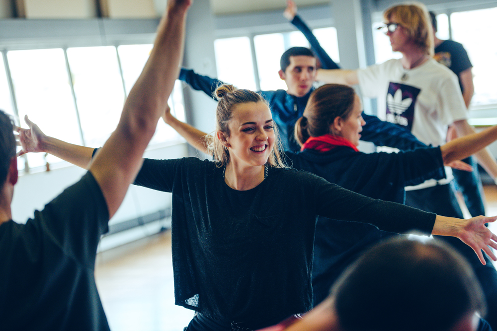 Young people moving around a studio space, arms in the air and smiling