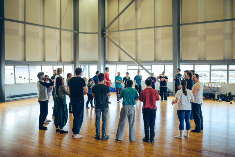 Young people in a circle in a studio, participating in a workshop.