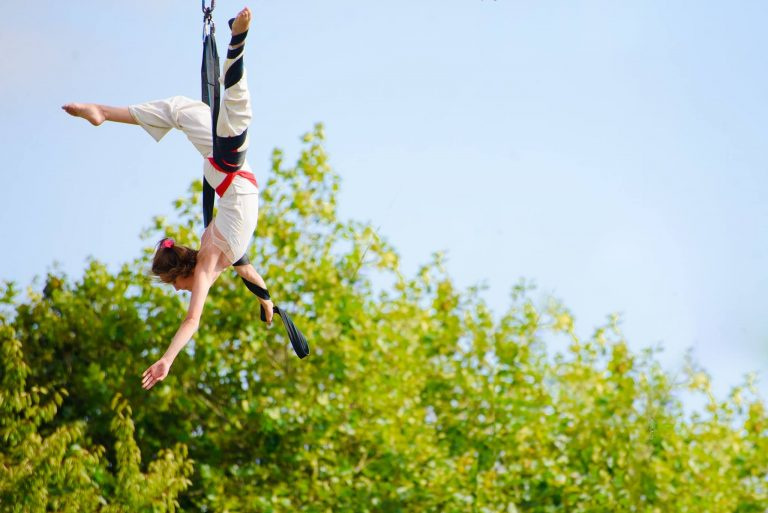 Extraordinary Bodies artist Aislinn Mulligan performing aerial circus, using straps, moving through the air.