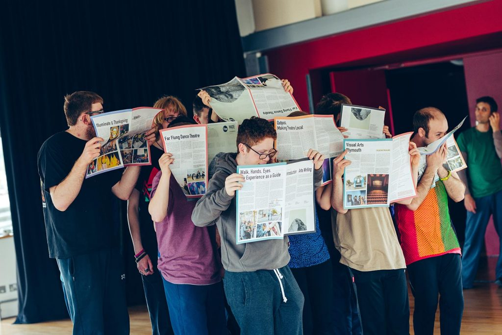 Group of 8 people standing in rows, hiding their faces whilst reading and holding up newspapers.