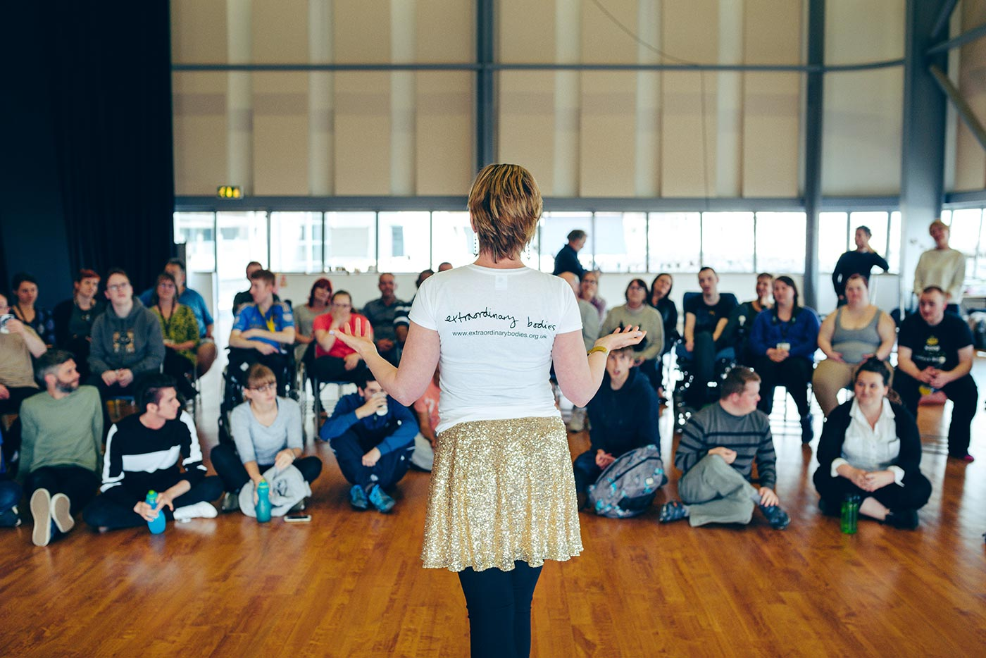 Claire Hodgson wearing a sparkly skirt with hands raised, in front of a large group looking up at her.