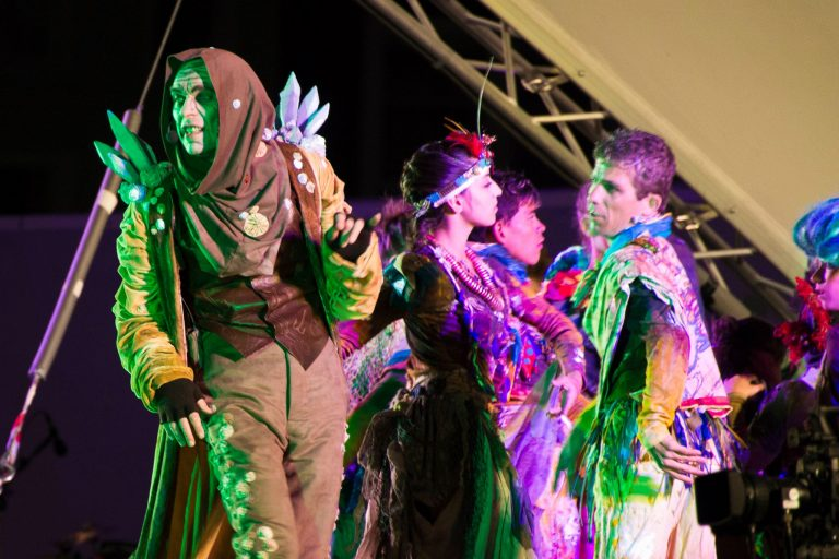Performers on stage in costume, moving on stage with bright atmospheric lighting.