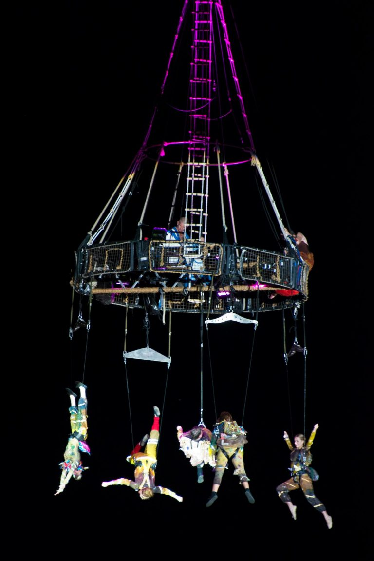 Performers suspended in the air from a crane and aerial equipment.