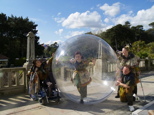 Performers of Breathe pose in costume, with one girl running in a giant bubble.