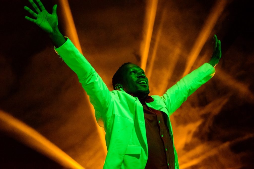 David Ellington, performing on stage with arms in the air, illuminated by a green light, with a bright orange light glowing behind him.