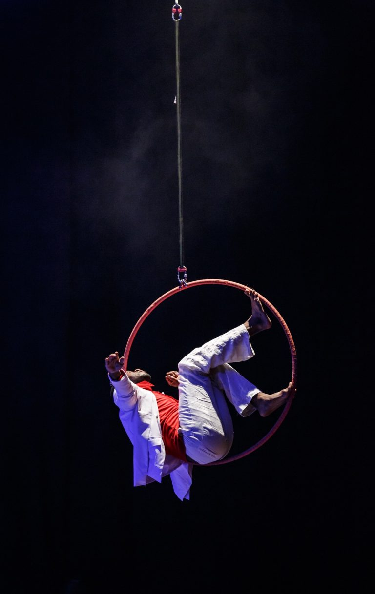 David Ellington performing aerial solo piece on stage, against a dark, black backdrop, he is illuminated wearing red top and white trousers & jacket. Suspended in the air, his arms outstretched.