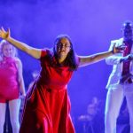 Nina comes ahead centre stage in a long red dress, her arms outstretched. Karina and David are in the background, gently moving. The lighting is purple and moody.