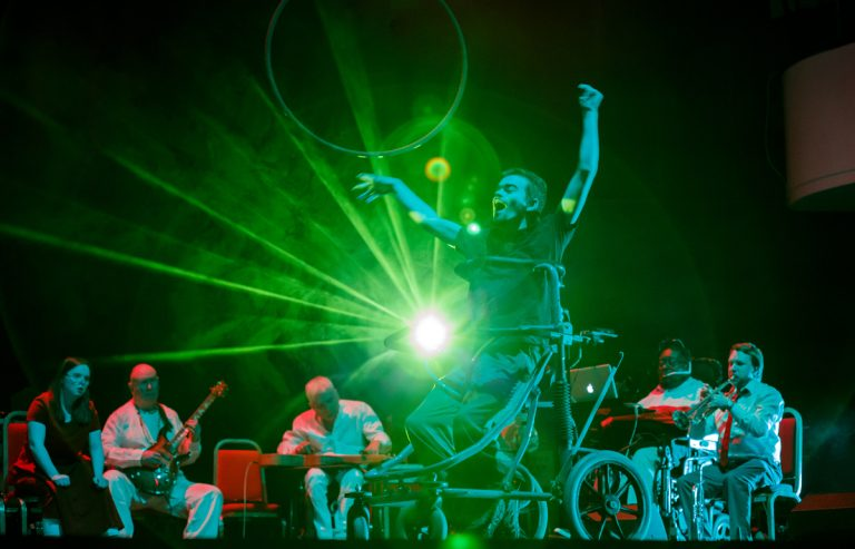 David Young moves across centre stage in his wheelchair walker, the Paraorchestra musicians seated behind him. David's arms reach up, it looks like he is catching the light from the bright green lasers coming from back of the stage.