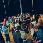 Extraordinary Bodies Creative Explorations workshop in Plymouth - a room full of people dancing, moving and smiling together.