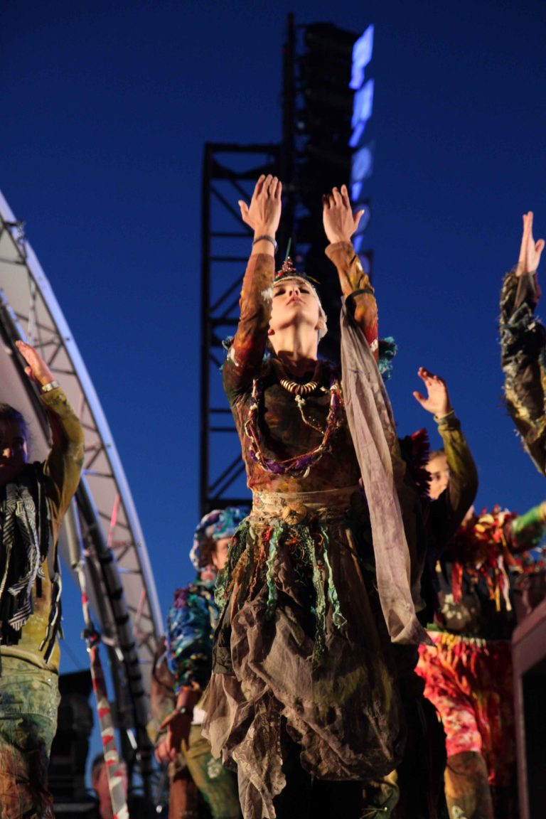 Performers on stage in costume for Breathe, London 2012 Olympics - performers are reaching their hands to the sky