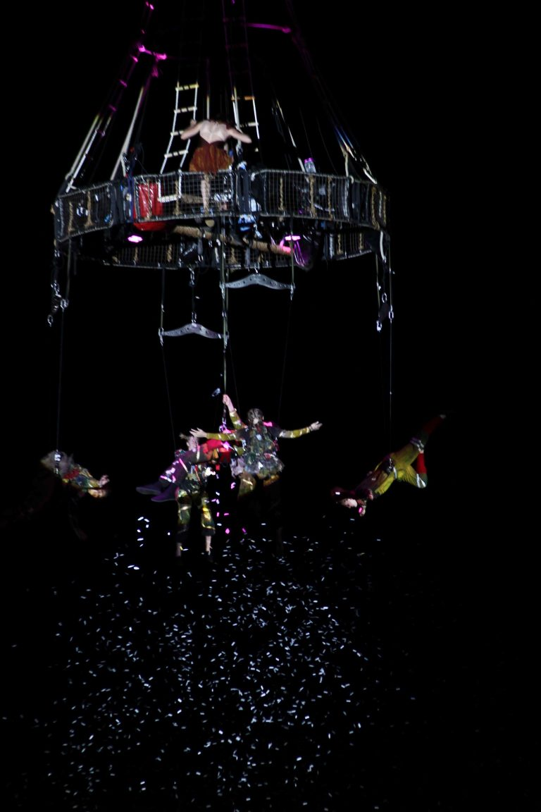 Performers suspended in the air from a crane and aerial equipment, with confetti flying around them.