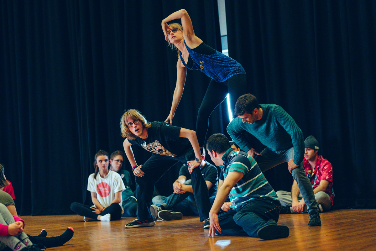 Participants from the Creative Explorations workshop perform movement to a group of people sitting down.