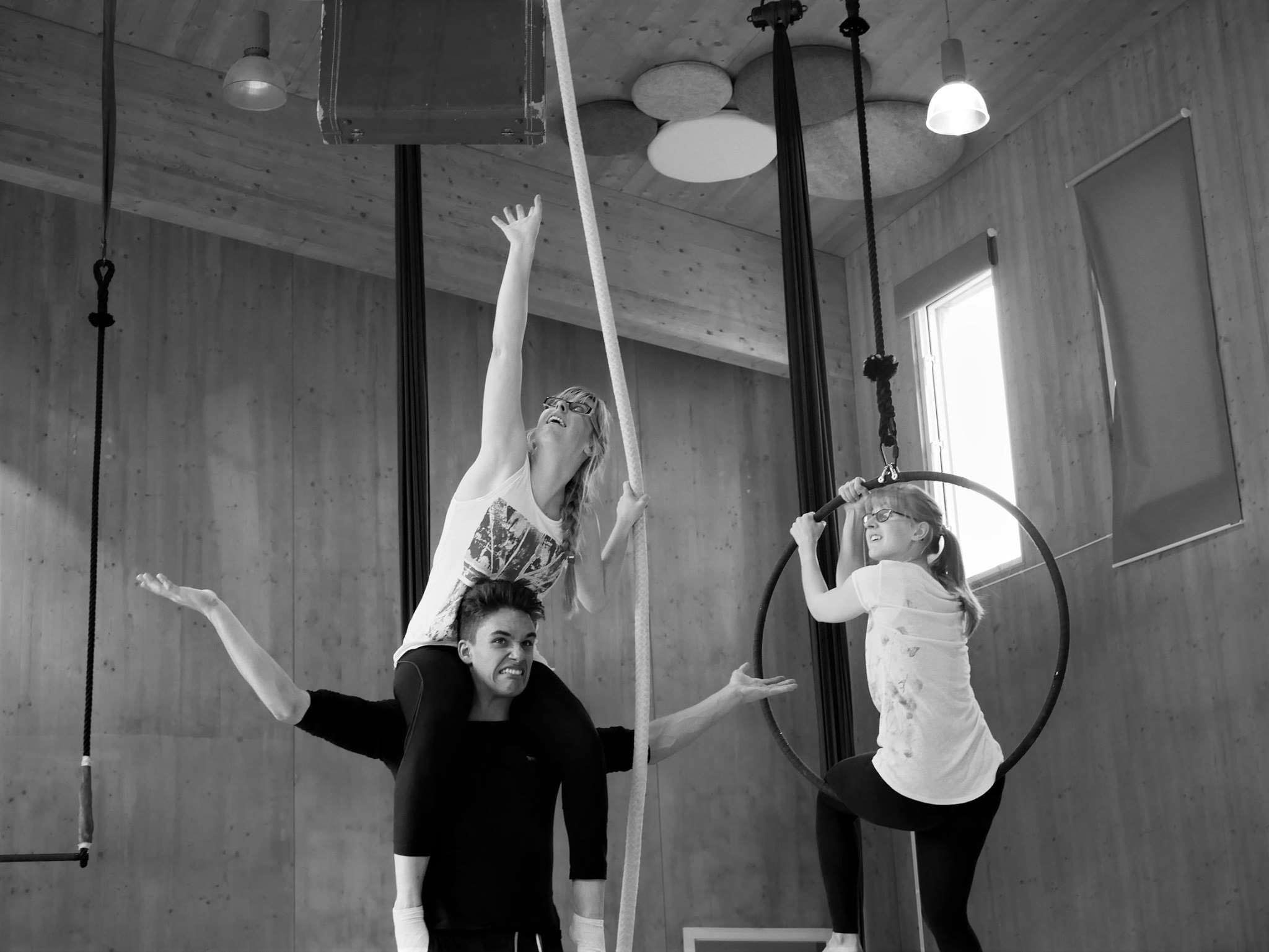 EBYA members devising Becoming: Clarissa sits on Anthony's shoulders, reaching for a suitcase that is suspended in the air. Freya watches them whilst sat in aerial hoop.