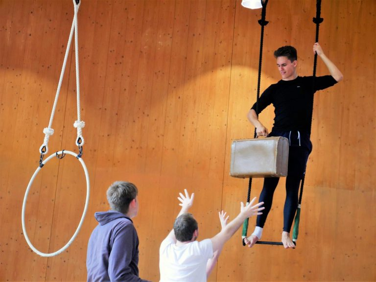 EBYA members devise Becoming - Anthony stands on the trapeze holding a suitcase, Shane and Luke are reaching for the suitcase.