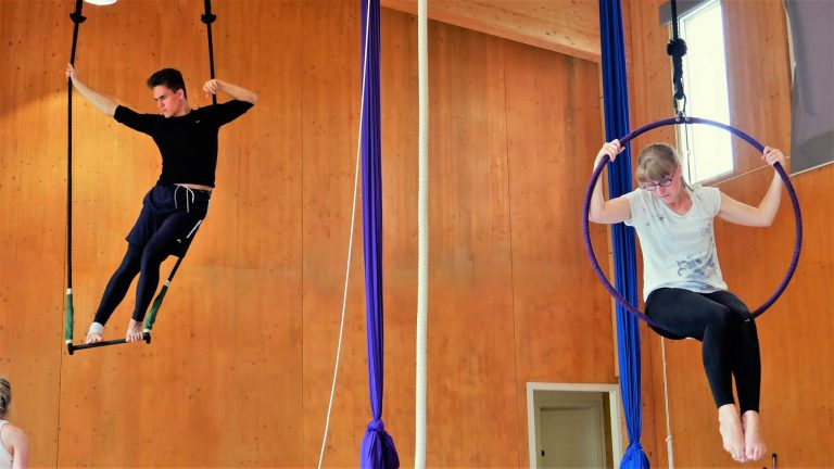 EBYA members devise Becoming - Anthony stands and stretches on the trapeze and Freya sits in the aerial hoop looking down.
