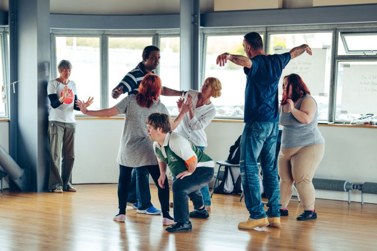 Participants from the Creative Explorations workshop moving and dancing around the room.