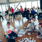 Creative explorations workshop with Extraordinary Bodies artists - participants sit in groups around the room, discussing questions and prompts. Lots of people are smiling and laughing.