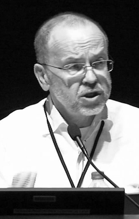 Black and white photo of Graham, talking into a microphone