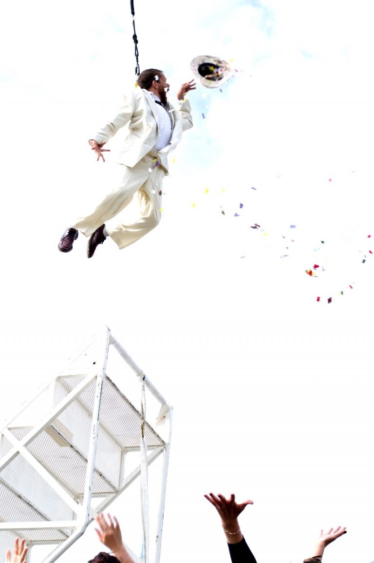 Extraordinary Bodies artist Jamie Beddard performs in Weighting, dangling in the sky surrounded by confetti.
