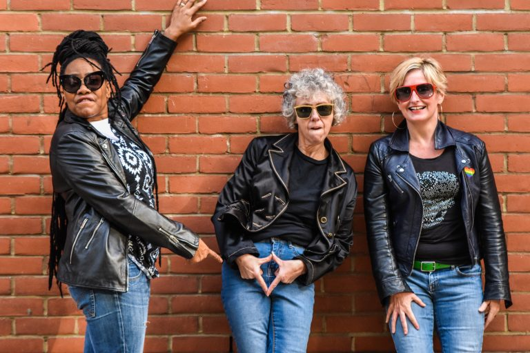 Three women in jeans and leather jackets, wearing sunglasses. Jacqui points to Karen, who's gesturing the female body by holding her hands in a diamond shape over her crotch. Claire laughs on.