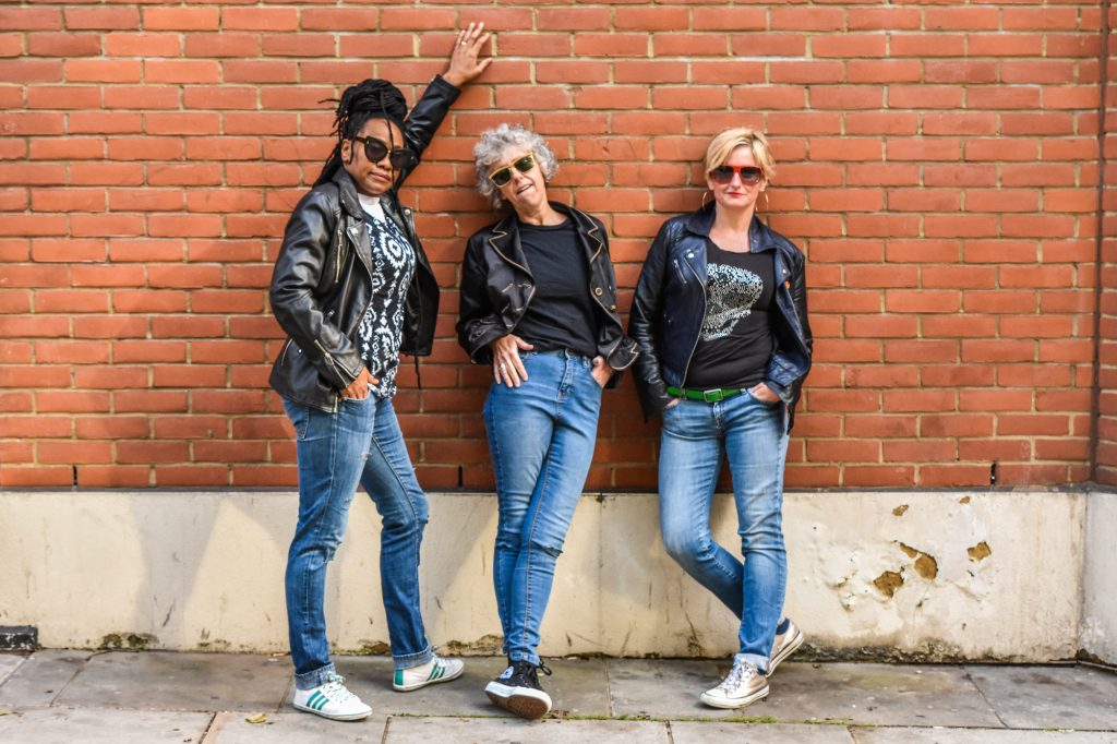 Three women in jeans and leather jackets, wearing sunglasses. They look cool. They pose to the camera leaning against a brick wall, with attitude.