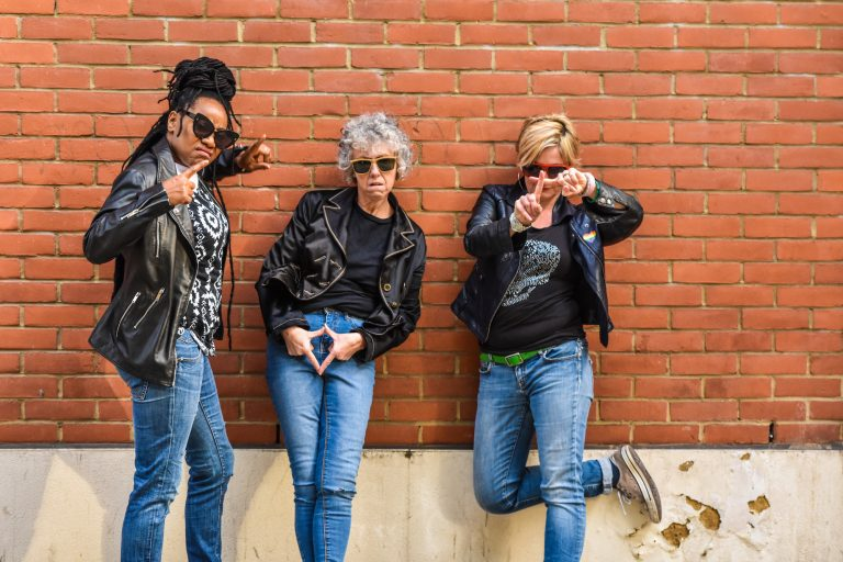 Three women in jeans and leather jackets, wearing shade and joking to the camera about midlife.