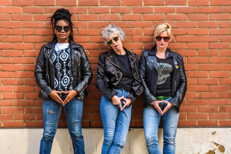 Three women in jeans and leather jackets, wearing sunglasses leaning against a brick wall. They all gesture the female body by holding their hands in a triangle over their crotch. Their expression's unimpressed - they look like they have something to say about it.