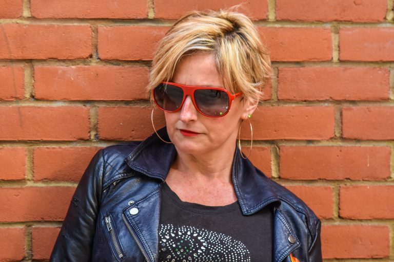 Portrait of Claire - white female, 50, short blonde hair. Rocking red-framed sunglasses and large gold hoops. She oozes attitude.