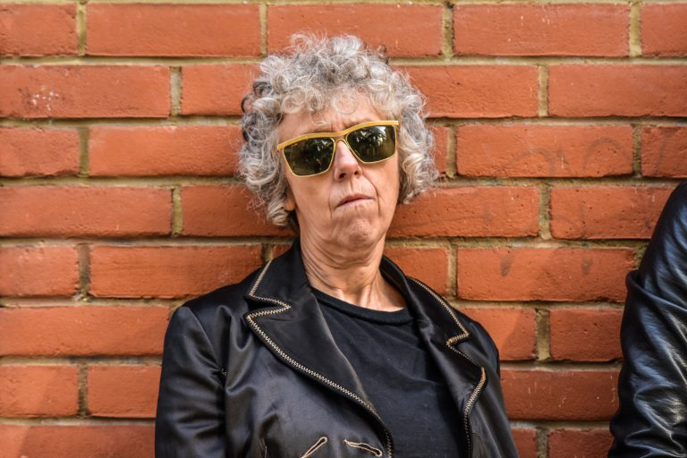 Portrait of Karen, white female, 50-something, short curly grey hair. She's rocking her black leather jacket and yellow-rimmed sunglasses. She oozes attitude.
