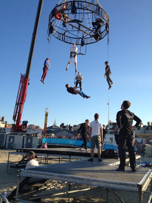 Performers rehearsing aerial circus routine on a crane, dangling 20ft from the floor.