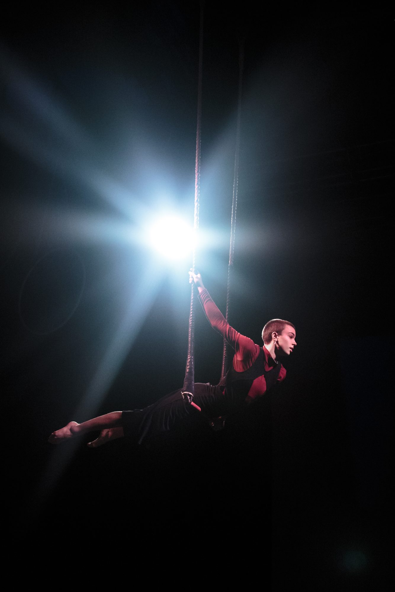 Performance of becoming: One member balances on a trapeze with legs pointed straight and arms raised above head. A bright light behind illuminates the performer.