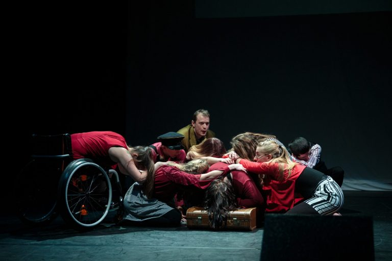Performance of Becoming - EBYA members are gathered centre stage crouched and kneeling down in a circle. Everyone wears red/grey/black clothing.