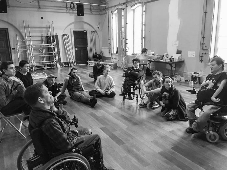 A group sit in a circle, in a well-lit studio space. Scaffold structures around the room. Everyone is listening carefully. (black & white photo)