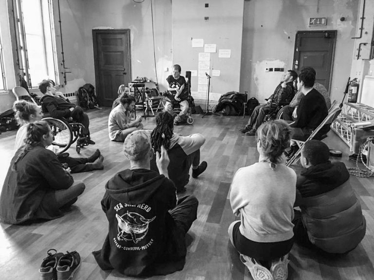 Photo from the back of a studio room, looking over the shoulders of the group, mostly sitting on the floor. Everyone looks ahead to John Kelly, sat at the front of the room. (Black & white photo)