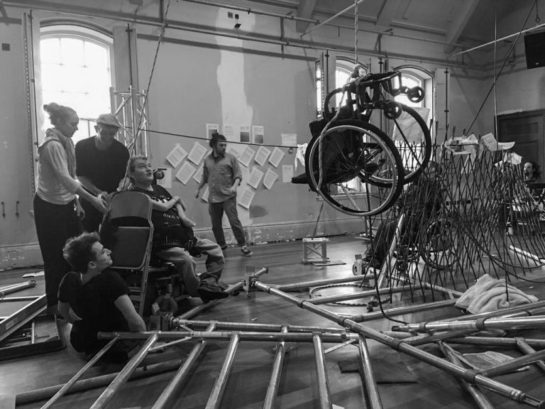 The group hoist a wheelchair above dismantled scaffold structure and other equipment. (Black & White photo)
