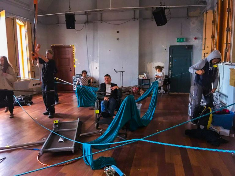 Jamie Beddard is in the centre of a studio, entangled in rope - with material draping across sections of the room. Scaffold equipment is scattered around the floor.