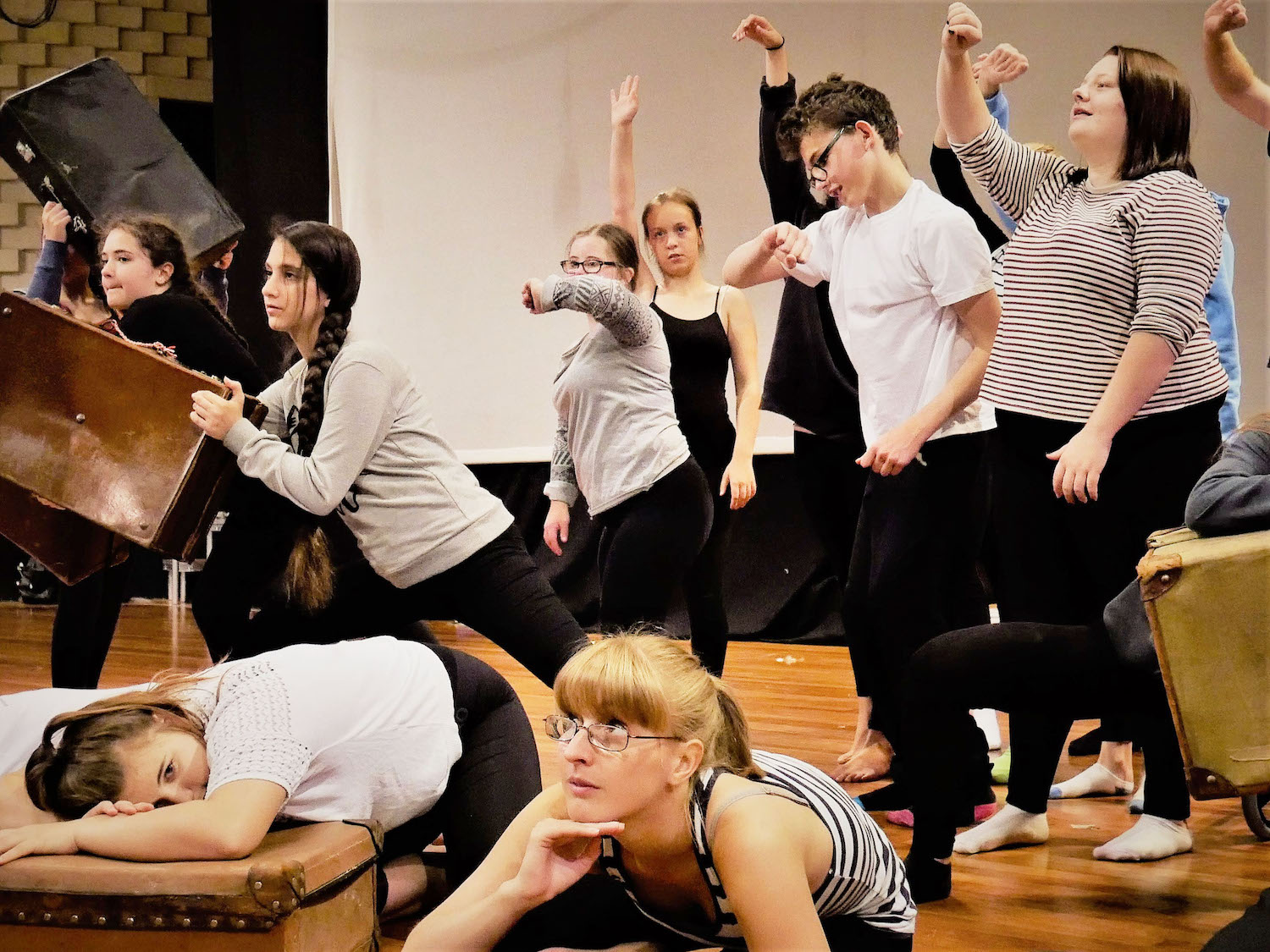 Ensemble rehearsing - some of the performers lay on the floor, hunch over suitcases and some standing with arms outreached, some looking at the time,