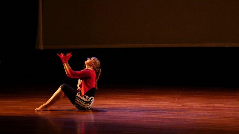 EBYA member Freya performs a floor dance solo on stage.