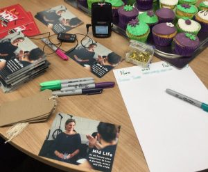 A table full of pens, swing tags, postcards and cakes, with a voice recorder ready to interview women.