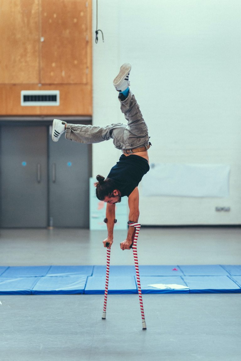 Dergin Tomak dances, balancing on his crutches, with his legs raised up in the air, during an Extraordinary Bodies residency at the National Theatre