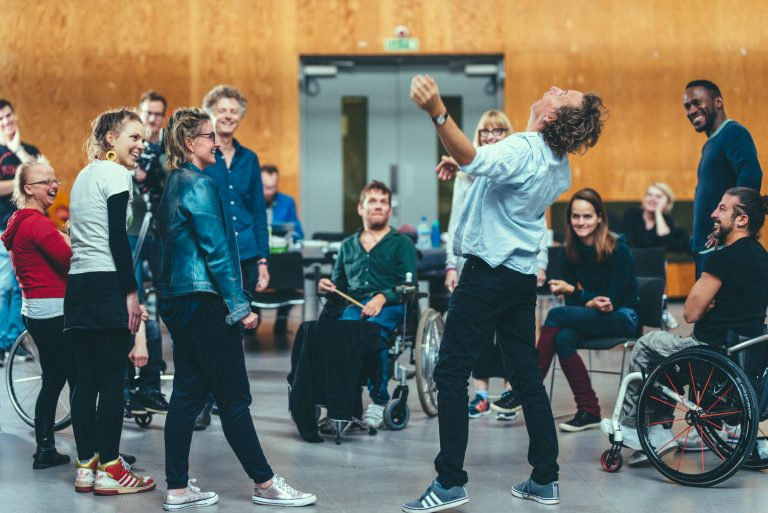 Extraordinary Bodies Artists and Creative Team in residency at National Theatre Studios, moving and laughing in the room, watching Ted Barnes dance in the middle of the room.