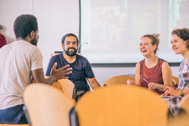 A small group of people sit in a room with lots of scattered chairs - it looks like a break from a workshop. They are talking and smiling together.