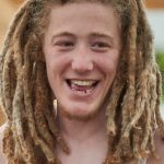 Hugo, a young white man, with light brown/blonde dreadlocks to his shoulders and a big smile!