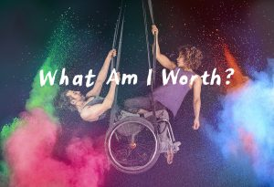 A white man in a wheelchair is suspended from aerial straps, with a strong black woman kneeling from his lap, pulling herself up on aerial straps. There is powdered paint billowing around the two circus artists in pink, green, blue and orange. The text 'What Am I Worth' is across the middle of the photograph.