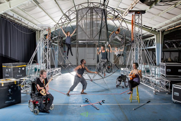 The 7 Extraordinary Bodies artists posing and moving around the new aerial set; a large circular structure suspended from both sides, with a cage-like feature and a ladder in the centre.