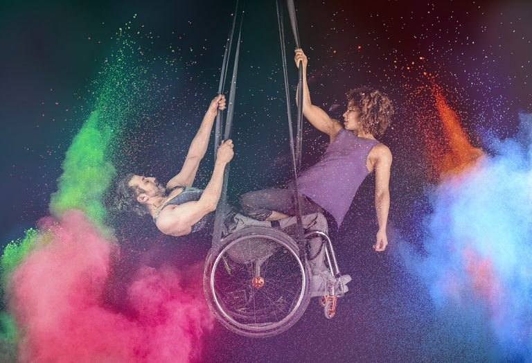 2 aerial artists suspended and entwined from straps: a white man in a wheelchair faces a muscular black woman - she is kneeling on his legs. There is an explosion of powdered paint around them in pink, green, blue and orange.